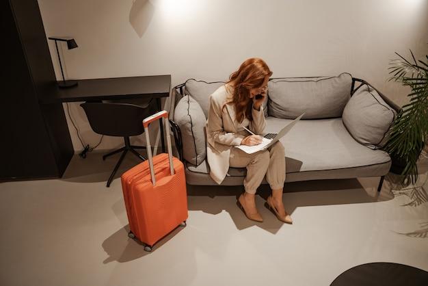 出張のコンセプト。スタイリッシュなビジネススーツとオレンジ色のスーツケースを身に着けた非常に忙しい赤毛の女性モデルは、ラップトップで動作し、出張中にスマートフォンで話します。若い実業家を