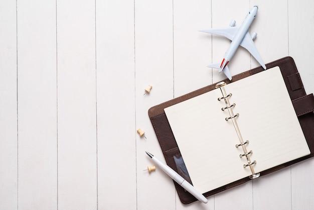 출장 개념입니다. 비행기와 텍스트를 위한 빈 열린 노트북입니다.