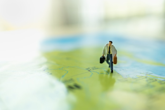 Business trip and travel concept. close up of businessman miniature figure with handbag suitcase running on colorful world map
