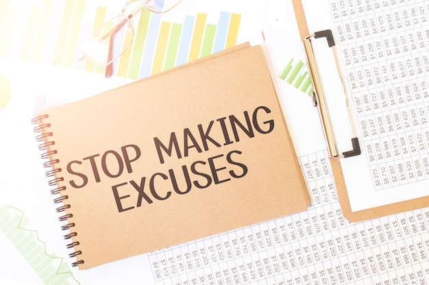 Business up graph on a sheet of craft colour notepad with stop making excuses sign. notepad on desk with financial documentation