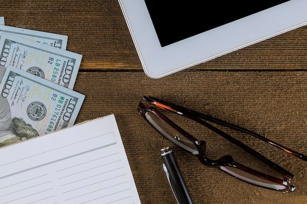 Business view from above on a wooden table - empty notebook and pen, dollar bills, glasses