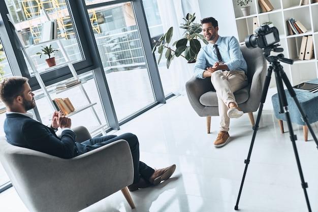 비즈니스 브이로그. 스마트 캐주얼 차림의 두 젊은이가 실내에서 새 비디오를 만드는 동안 이야기하고 있습니다.