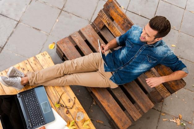 急ぐことなくビジネス。屋外でリラックスしながらデジタルタブレットを保持している笑顔の若い男の上面図
