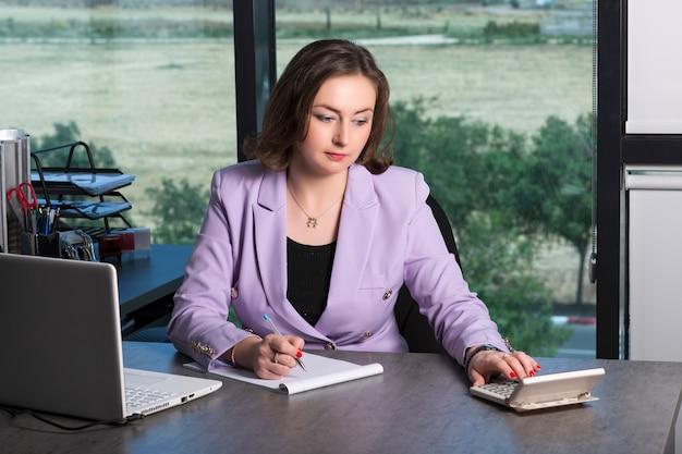 オフィスで紫色のスーツを着たビジネスウーマンの会計士は、電卓を使用してノートにデータを書き込みます。利益分析、税金と支払いの計算、財務諸表の概念の準備