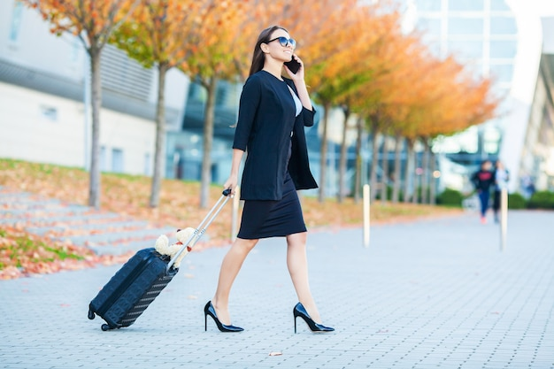 Business woman in airport talking on the smartphone while walking with hand luggage in airport going to gate.