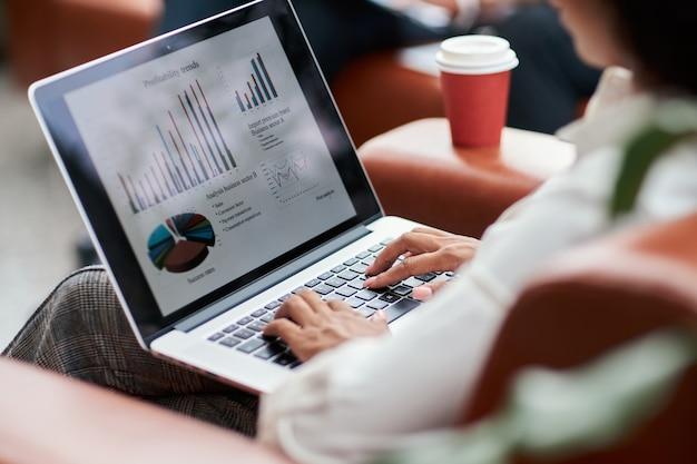노트북에서 재무 차트를 분석하는 비즈니스 우먼