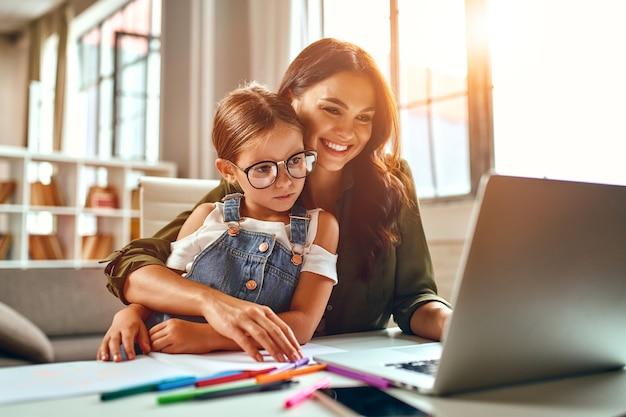 비즈니스 우먼과 엄마는 노트북에서 어린 딸과 함께 일하고 있습니다. 프리랜서, 재택근무.
