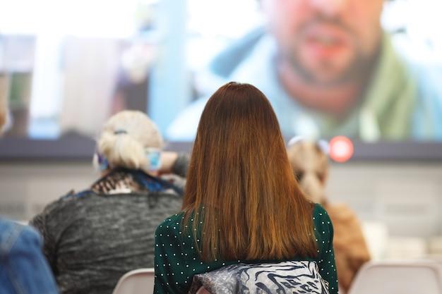 Деловая женщина и люди, слушающие на конференции