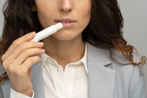 Business woman applying hygienical chapstick to her lips to prevent dryness and chapping in the cold season