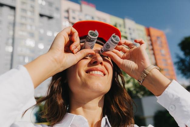 Архитектор бизнес-леди в каске просматривает долларовые банкноты как символ приверженности. бизнес