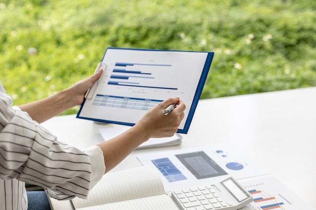 비즈니스 여성은 파트너와의 회의에 정보를 가져오기 전에 문제를 분석하고 솔루션을 찾기 위해 회사의 재무 문서를 보고 있습니다. 금융 개념입니다.