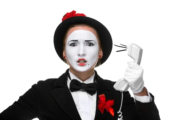 Business woman as mime holding a handset, isolated on white background. concept of grief and despair