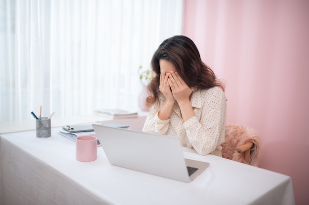 Business woman in bad mood failed and has problem while working with the laptop
