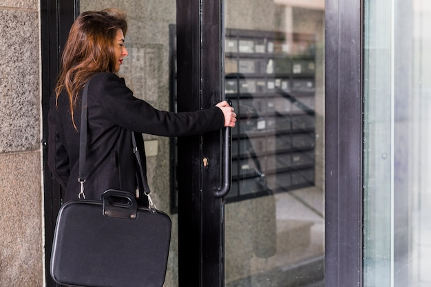 Business woman in black clothes entering building