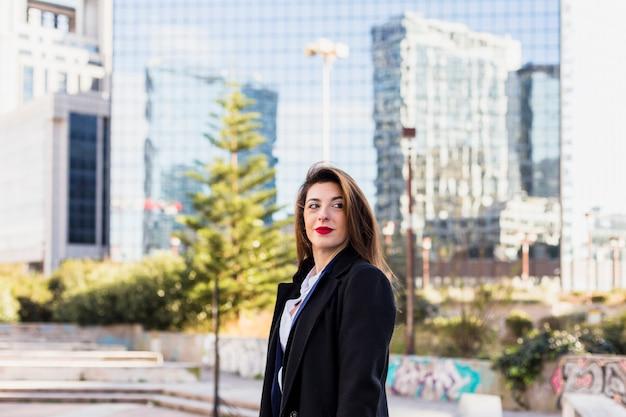 Business woman in black standing in street