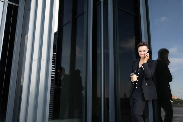 Business woman in a black suit on of a glass building of a business center