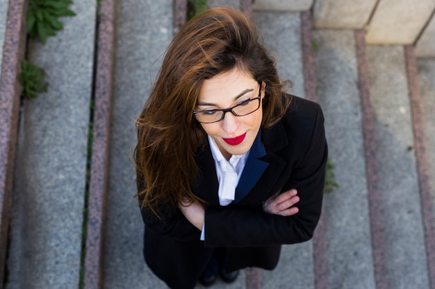 Business woman in black suit standing on stairs outside