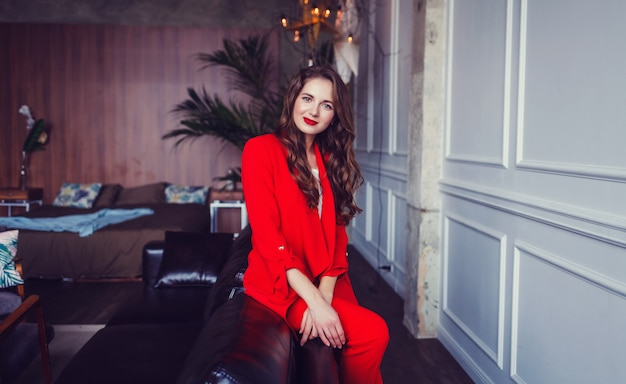 Business woman brunette hair in a red suit