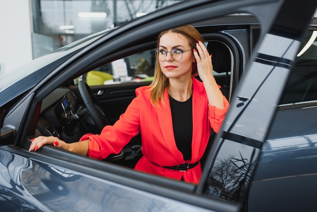ビジネスウーマンが自動車販売店で車を買う