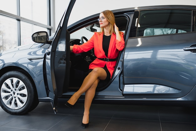 Business woman buys a car at a car dealership