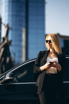 Business woman by the car in town using phone