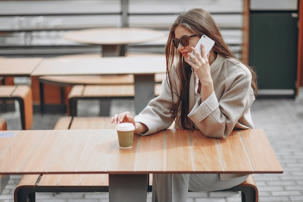 Business woman in a cafe drinking coffe, using phone