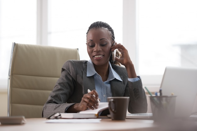 Business woman calling phone and writing