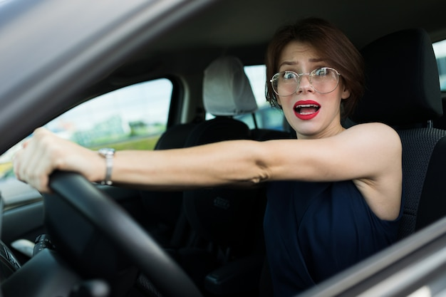 Business woman in car on the of a modern high-rise building