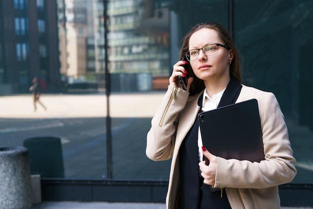 비즈니스 우먼 백인 민족성 양복과 그녀의 손에 노트북이 있는 안경을 쓰고 전화 통화를 하고 있습니다.