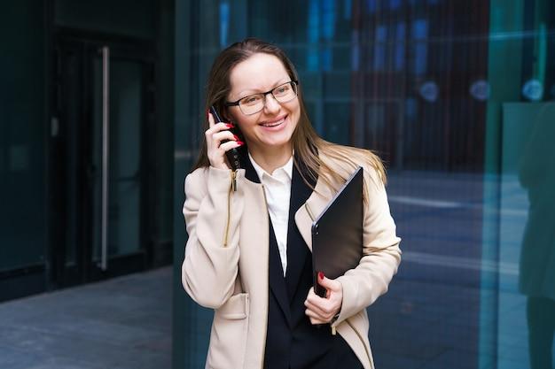 スーツと眼鏡をかけたビジネスウーマンの白人民族で、ラップトップを手に持って電話で話している...