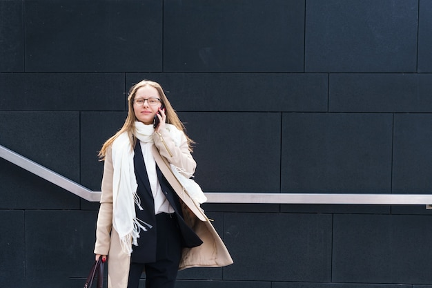 Business woman of caucasian ethnicity with glasses talking on the phone near the business center in ...