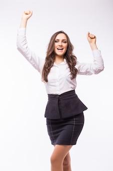 Donna d'affari che celebra felice allegro in abito bianco in tutto il corpo. vincitore incoraggiante in una danza gioiosa sul successo. giovane imprenditrice caucasica isolata sul muro bianco