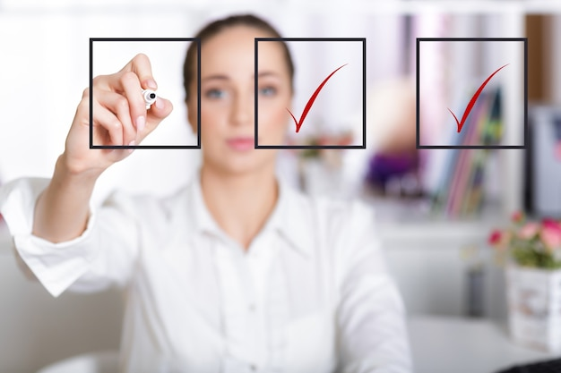 Business woman checking mark on checklist with a red marker
