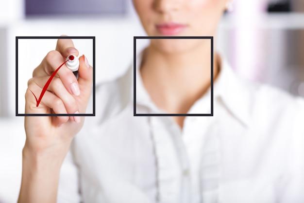 빨간색 표시가 있는 체크리스트에 체크 표시를 하는 비즈니스 우먼