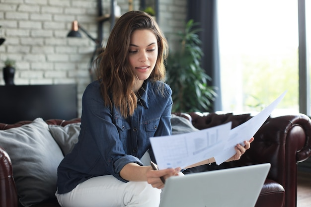 Деловая женщина, проверка бумажных документов в домашнем офисе, работает на ноутбуке из дома.