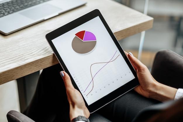 Деловая женщина проверяет графики и обновляет финансовый прогресс. девушка анализирует бизнес-модель на рабочем месте.