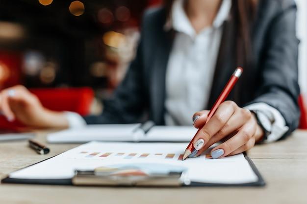 ビジネスウーマンはチャートをチェックし、財務の進捗状況を更新します。女の子は職場のビジネスモデルを分析します。