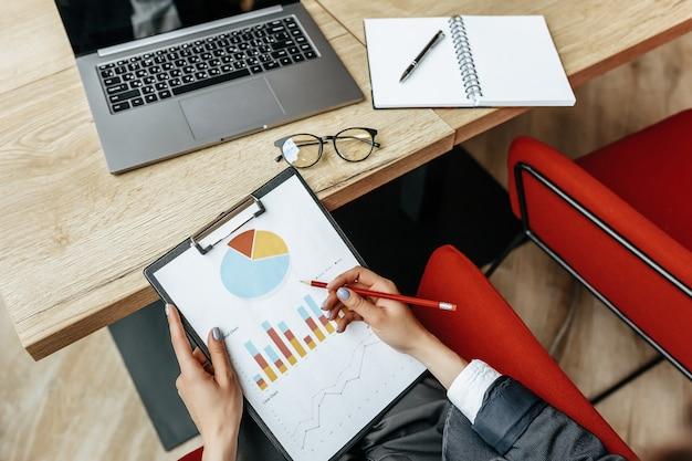 비즈니스 우먼은 차트를 확인하고 재정적 진행 상황을 새로 고칩니다. 그 소녀는 직장에서 비즈니스 모델을 분석합니다.
