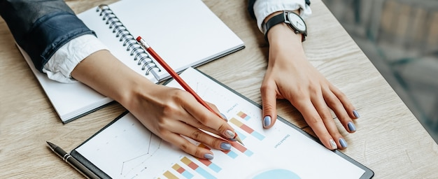 Business woman checks charts and refreshes financial progress. the girl analyzes the business model in the workplace.