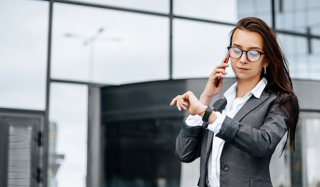 A business woman checks the time and talking on the phone in the city during a working day