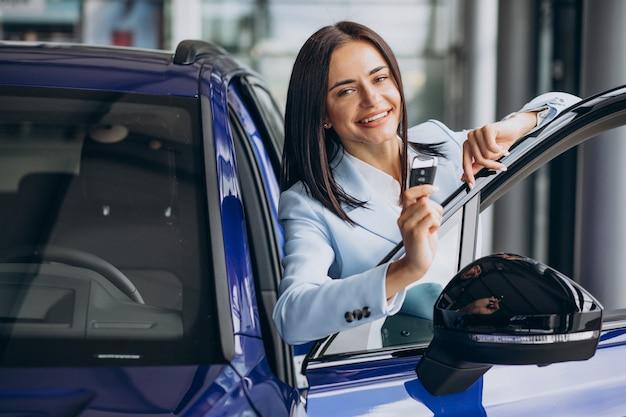 Donna d'affari che sceglie un'auto in uno showroom di auto