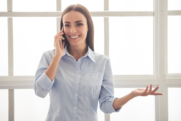 Business woman in classic shirt is talking on mobile phone.
