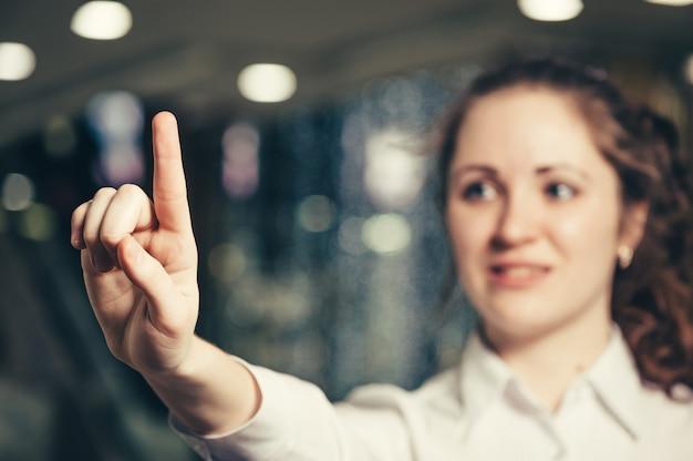 Деловая женщина нажимает на невидимую кнопку виртуального интерфейса