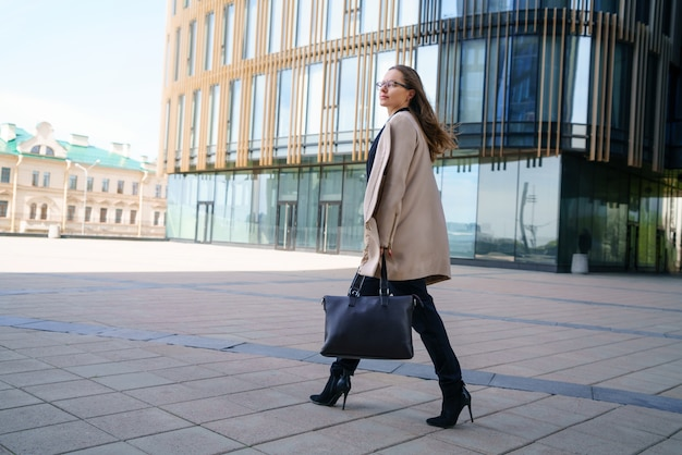 A business woman in a coat and suit, holding a bag in her hand, walks near the business center during the day.