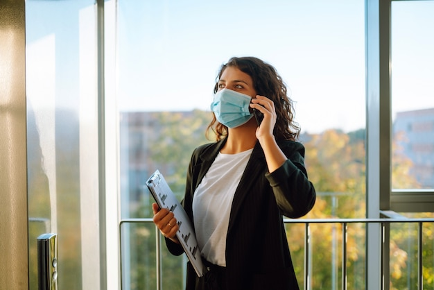 Business woman communicating over cell phone while wearing face mask.
