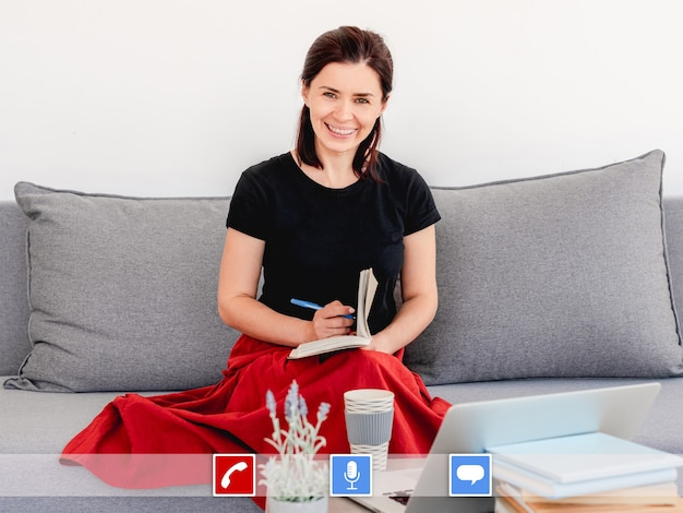 ペンとノートで自宅のソファに座ってウェブカメラと電話会議を使用して通信するビジネスウーマン