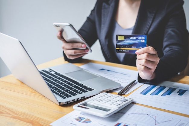 Business woman consumer holding smartphone, credit card and typing on laptop for online shopping and payment make a purchase on the internet, online payment, networking and buy product technology