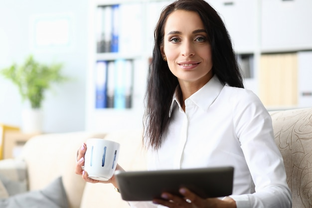 Business woman on couch runs laptop and cup