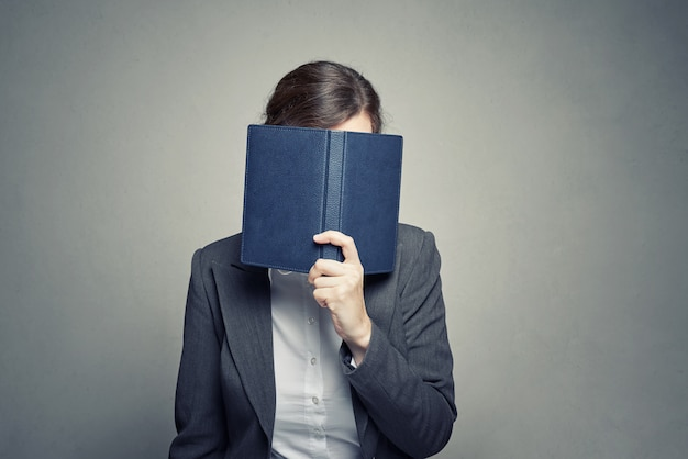 Business woman cover face with organizer diary