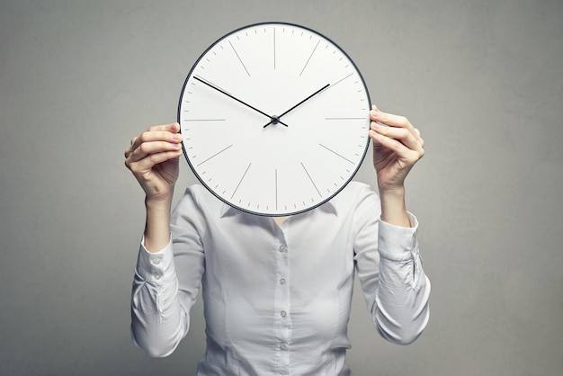 Business woman covering her face with clock